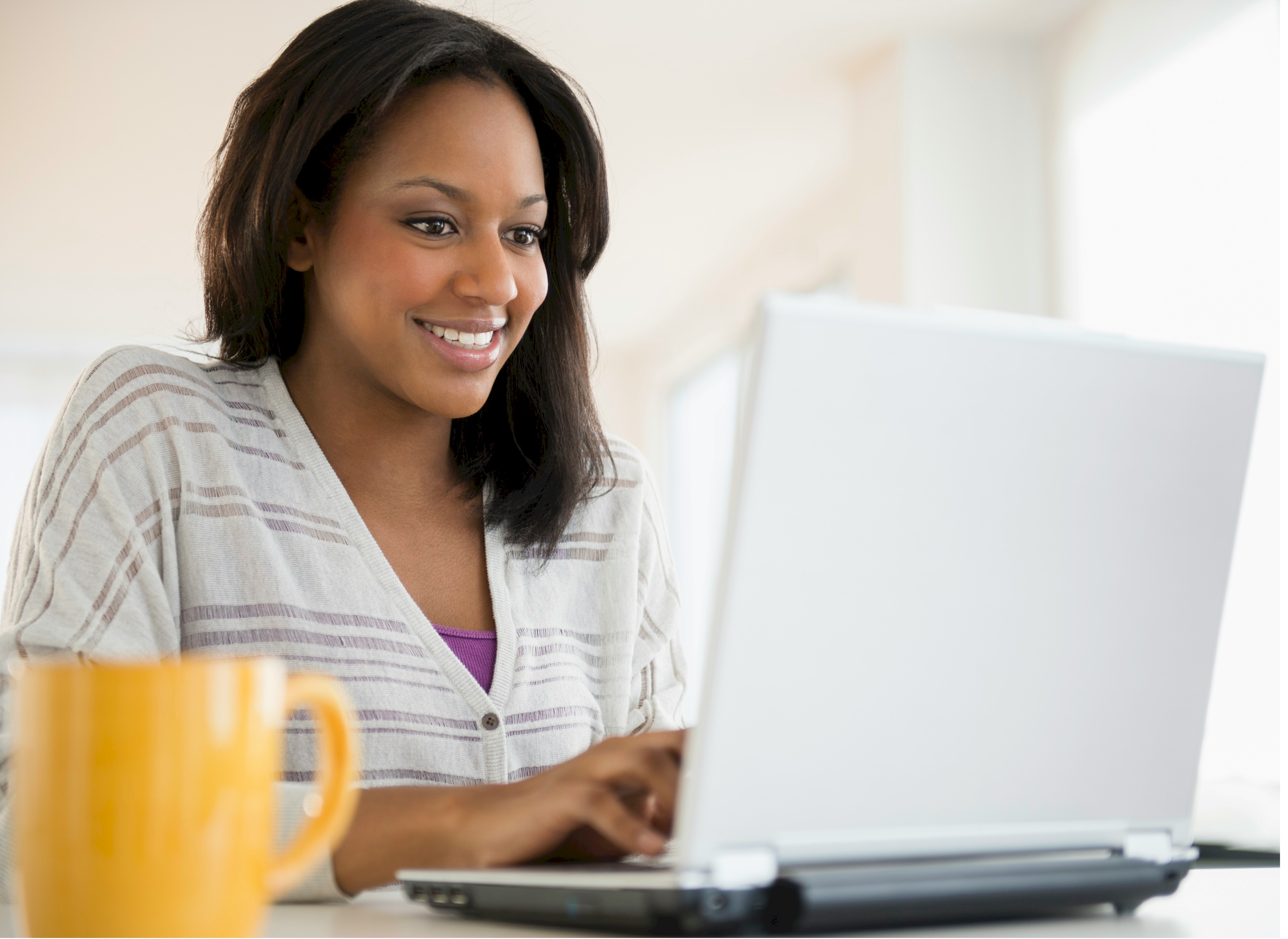 Black woman on laptop using Aspiration software